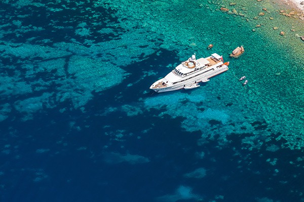 Luxury white pleasure yacht anchored near rocky coast of Corsica island, birds eye view
