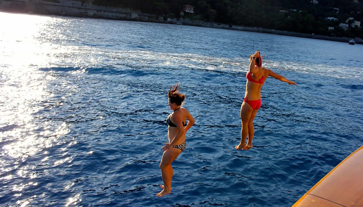 Two women jumping from their yacht into the ocean