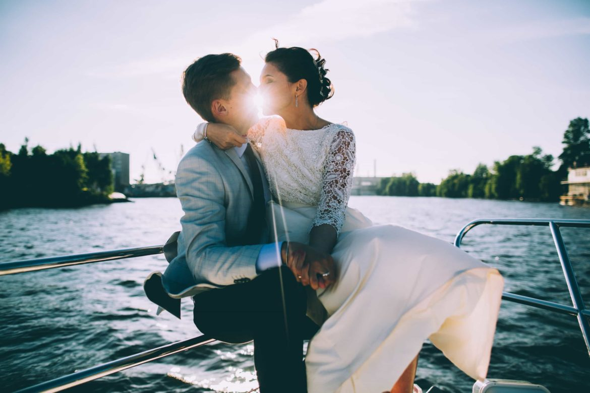 brunette newlywed couple kissing with the sun behind them, holding hands on the bow of a boat