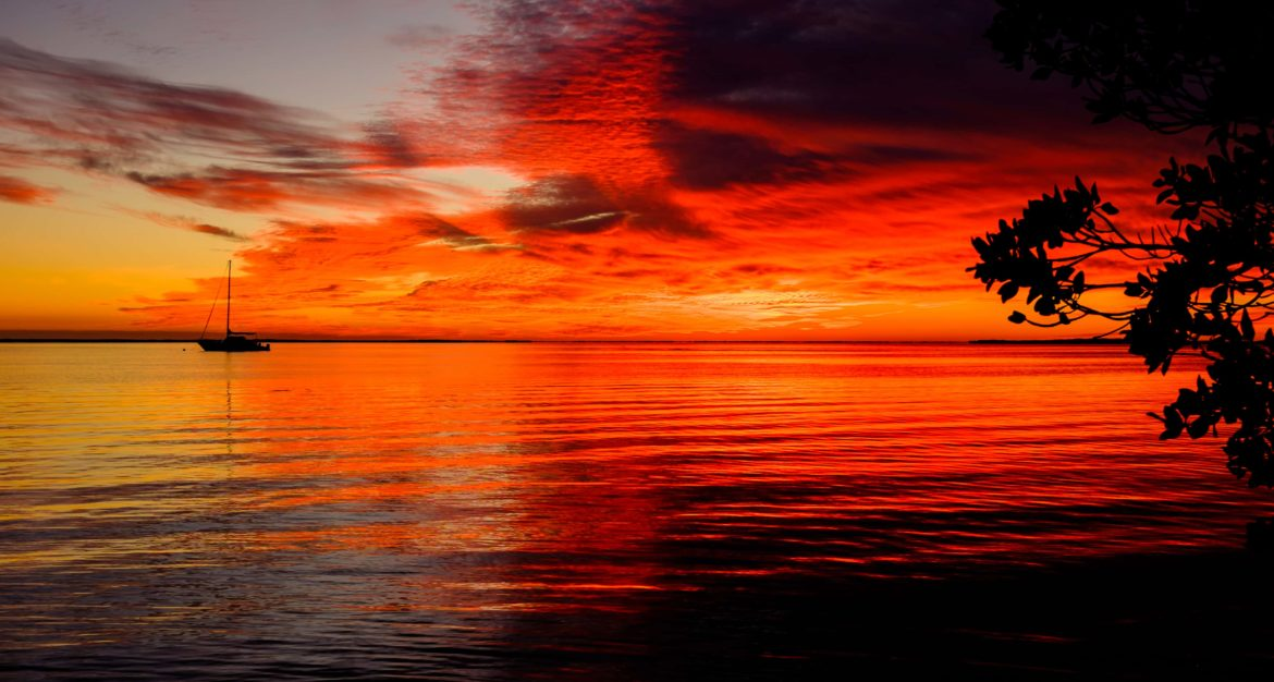 Sailing yacht shillouetted against a firy red and orange sunset