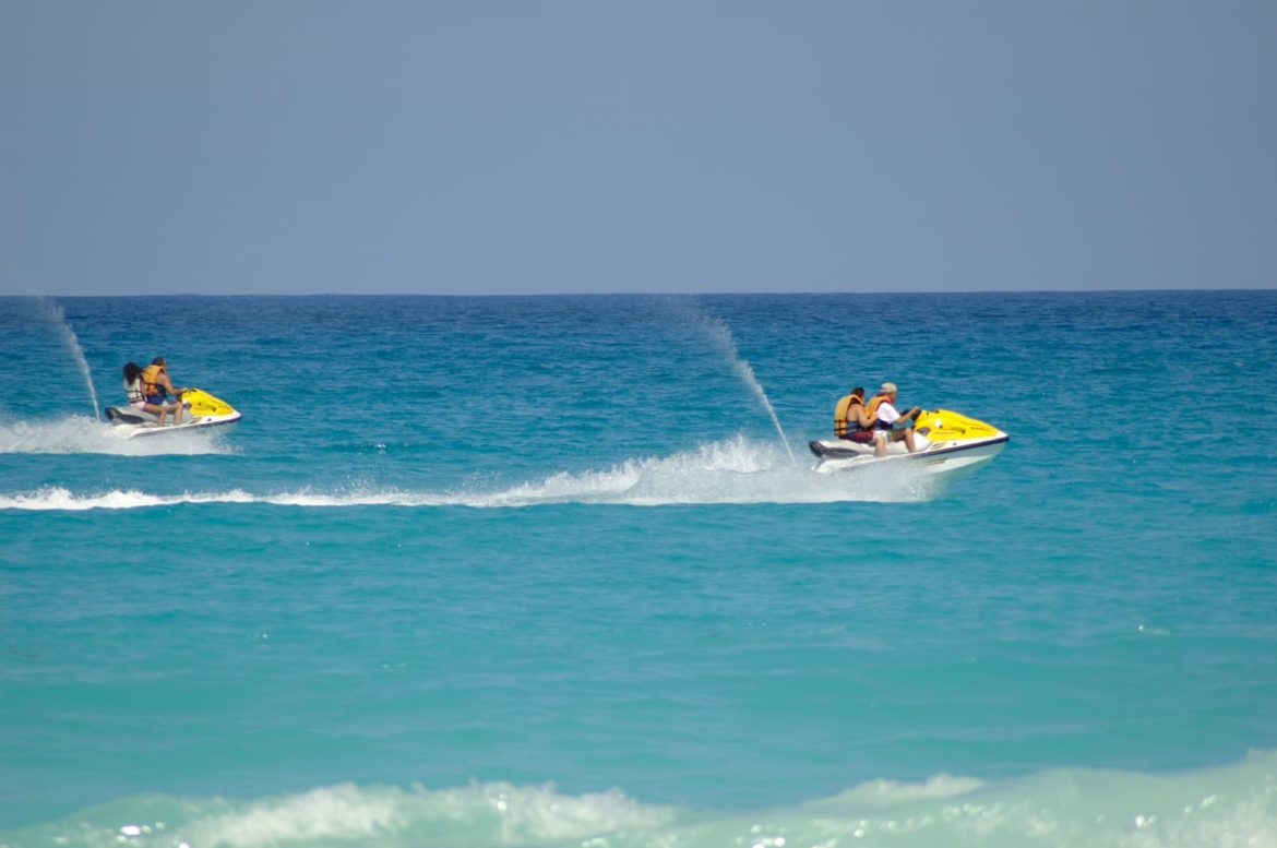 Yellow jet skis race across the water. Toys like these are available on your yacht charter.