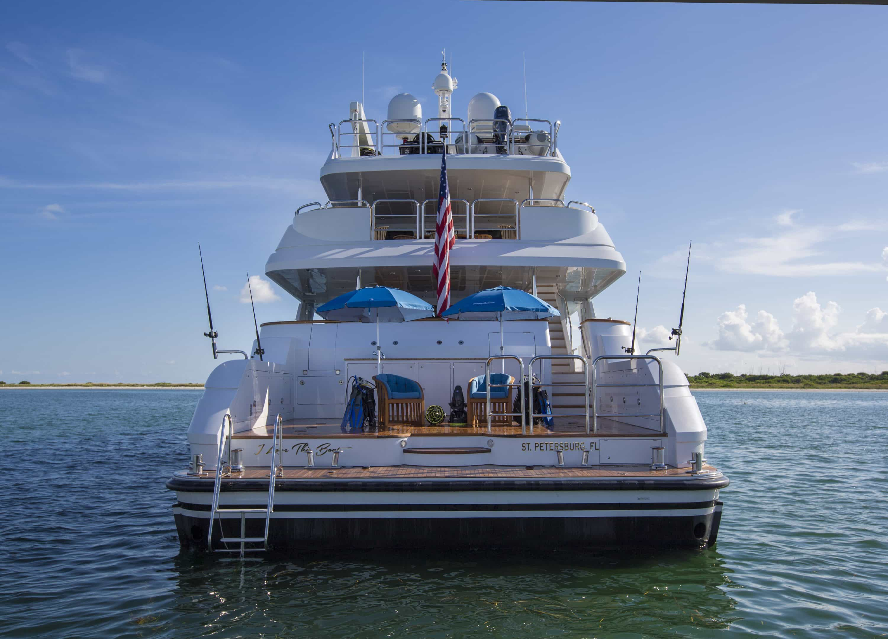 stern shot of I Love This Boat with three decks and beach club with chairs laid out