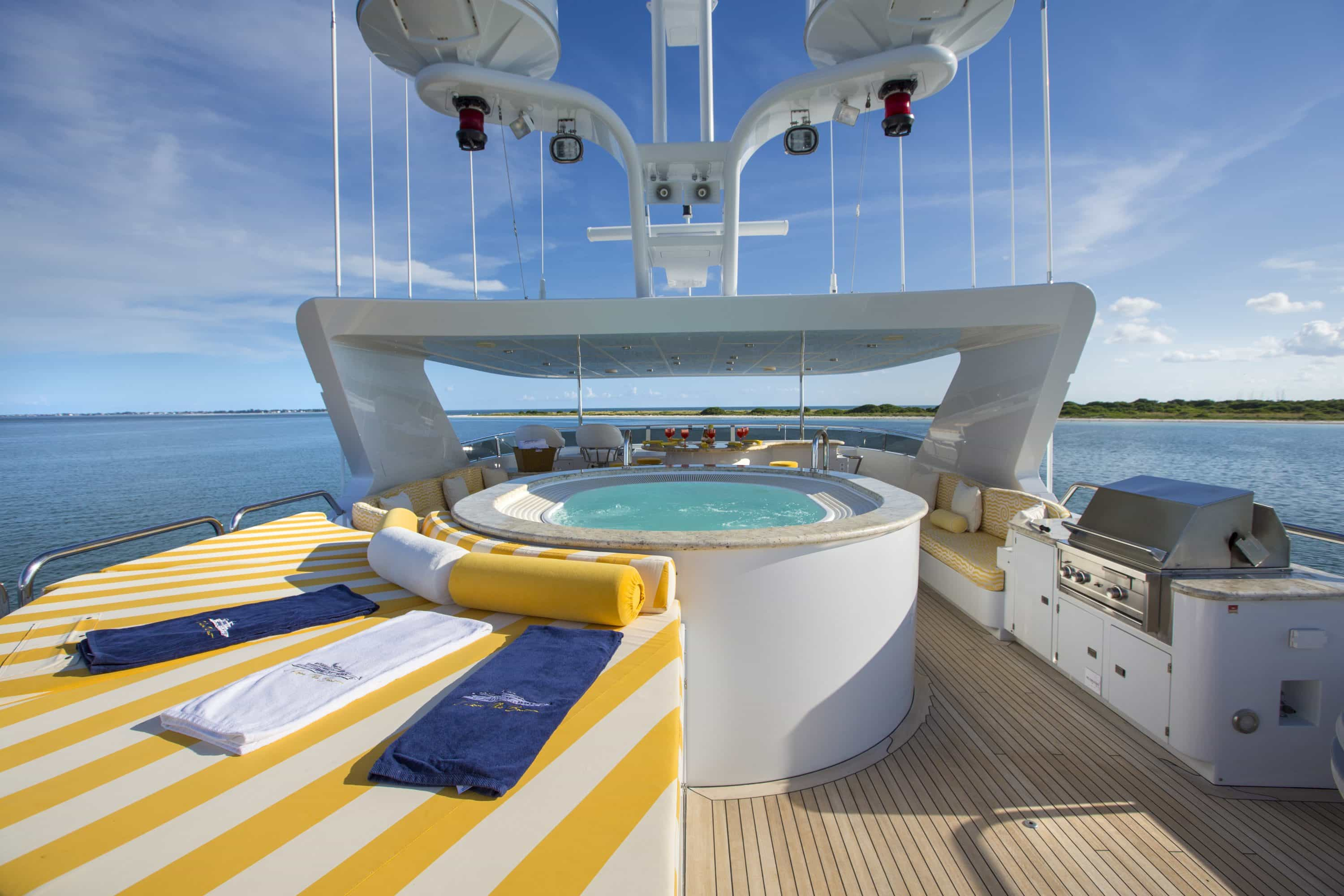 shot of jacuzzi on fly deck of I Love This Boat with yellow and white striped sun lounger and BBQ beside