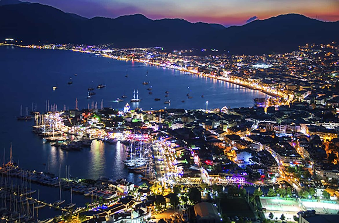 Marmaris Bay at night with yachts anchored offshore and colorful city lights onshore