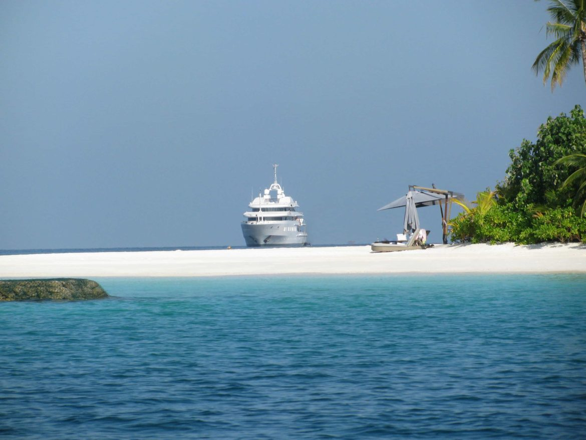 Luxury superyacht anchored near deserted beach