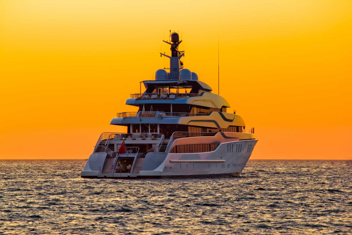 Dramatic shot of a luxury yacht at sunset