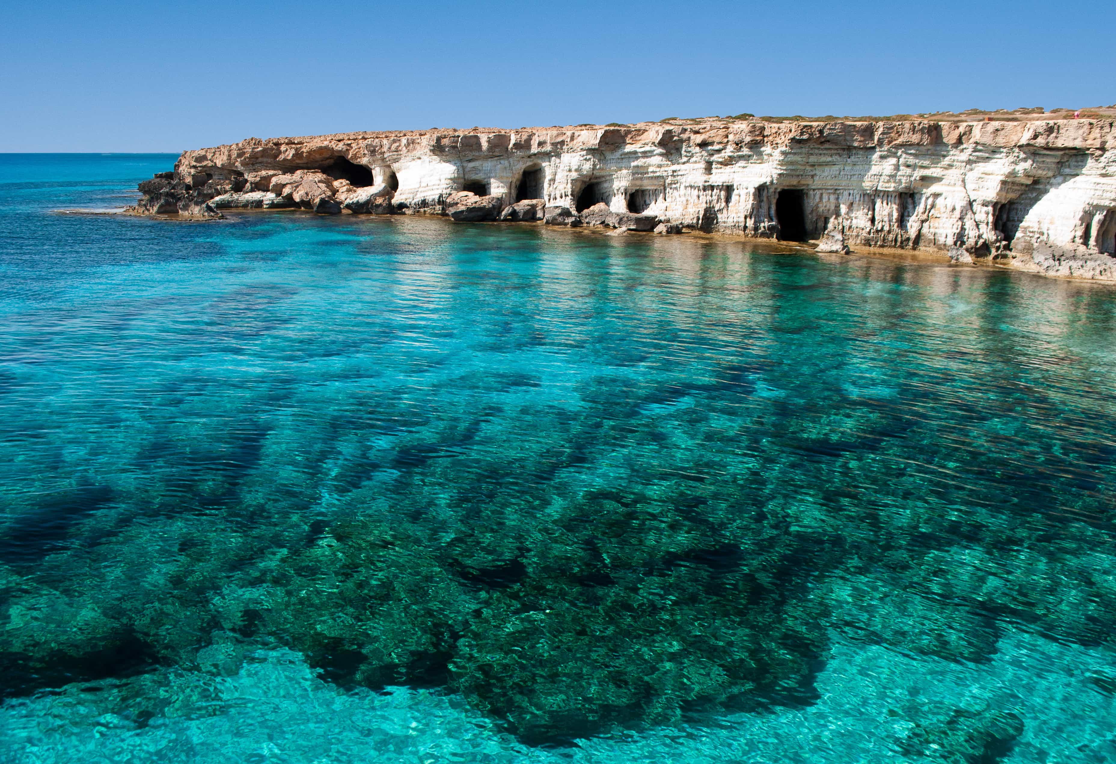 blue lagoon in Cyprus with rock cliffs around