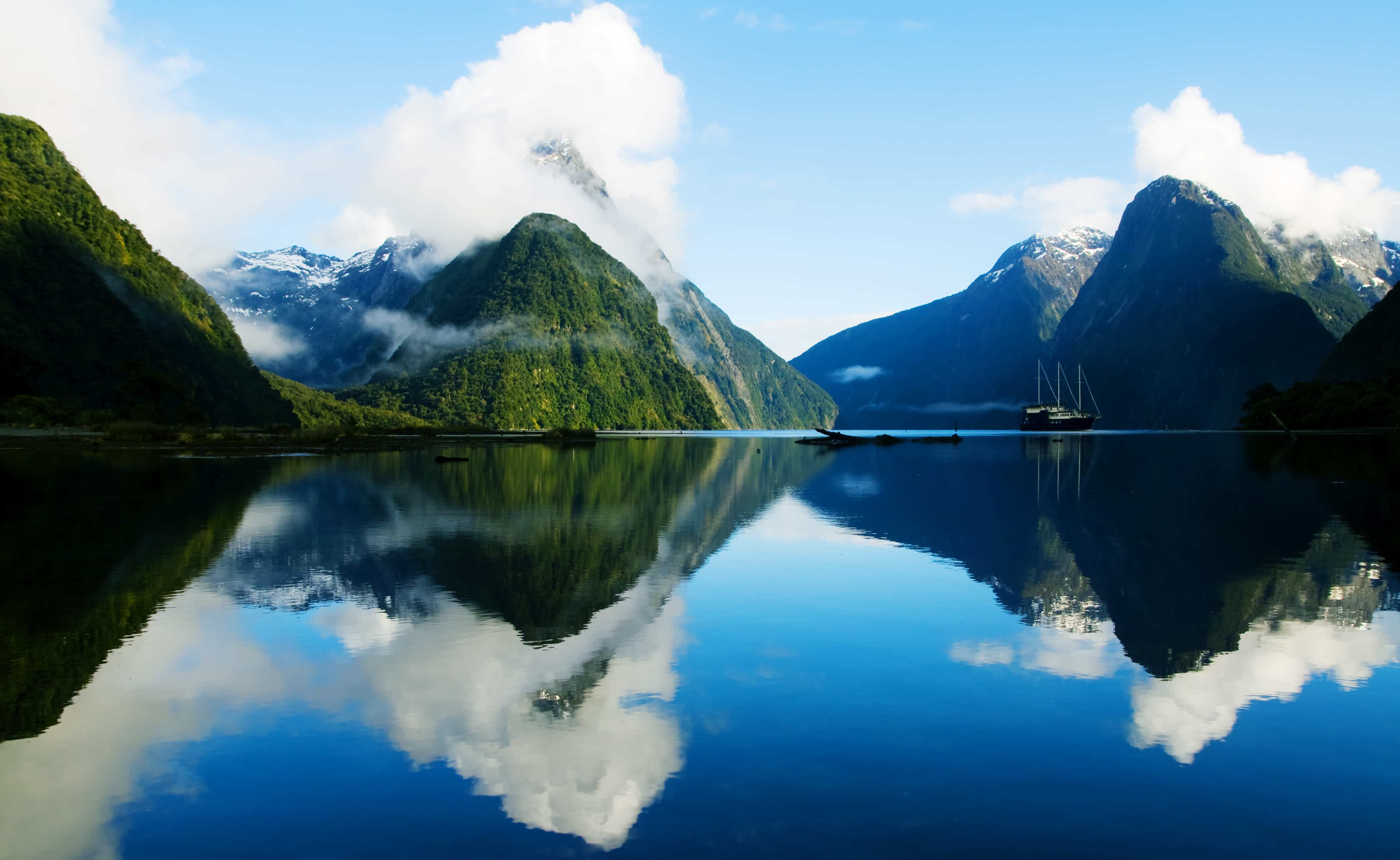 Emerald mountains rising from the glassy waters of New Zealand, a site to behold on your New Zealnd yacht charter