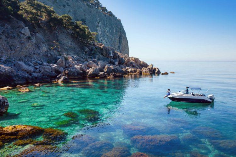 boat near cliffs of Greece on crystal blue water