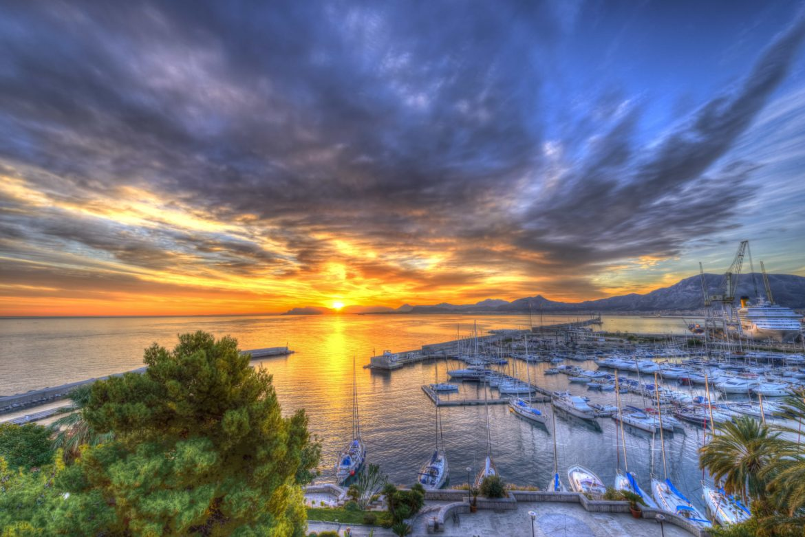 Sunset over a marina in Italy with sailing yachts docked