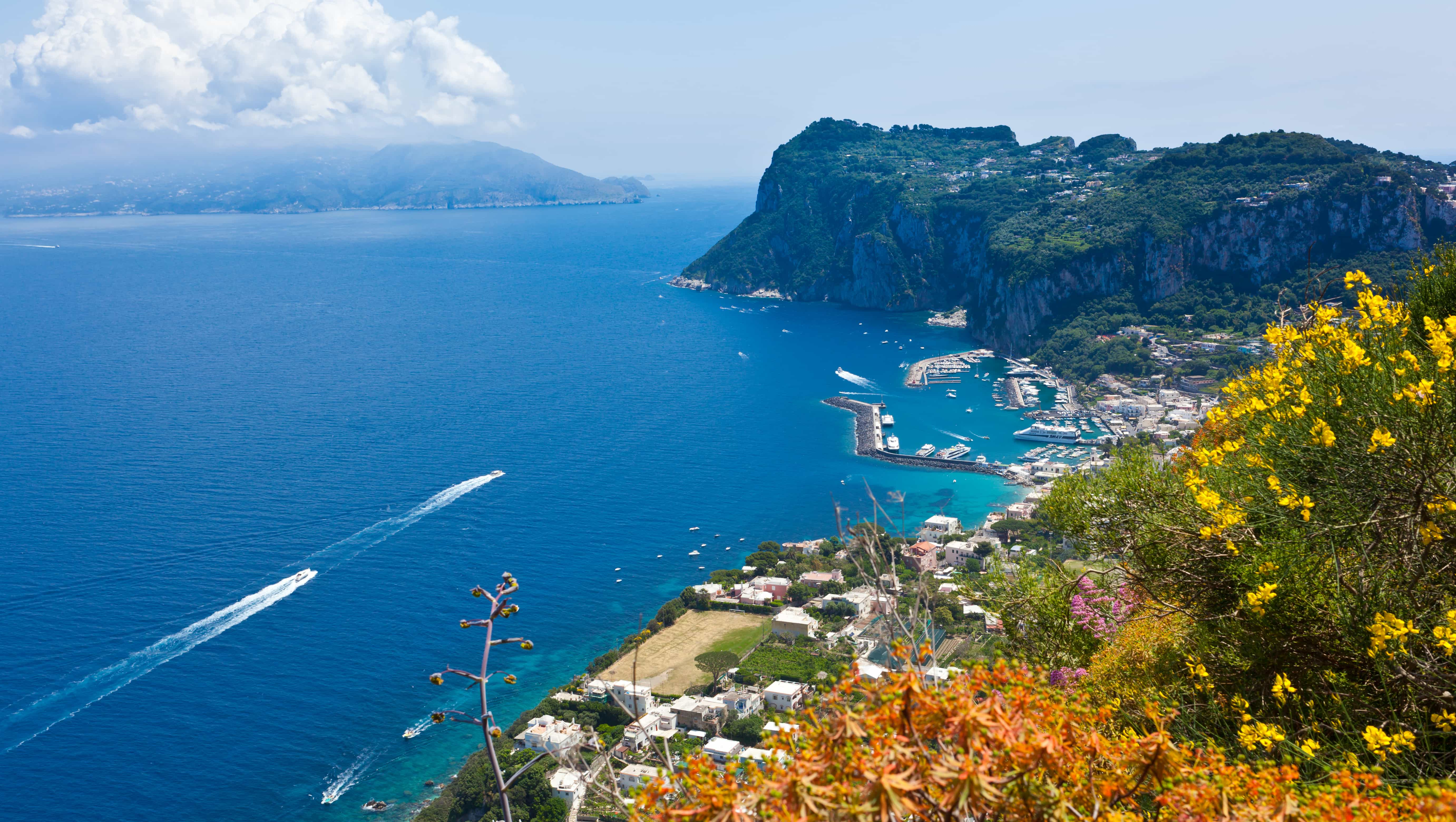 Bird's eye view of yachts sailing just off Italy's coast heading toward a small marina at the foot of a mountain