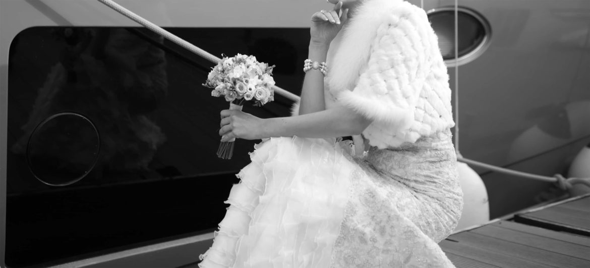 Close up black and white photo of bride details, holding flowers with shawl over shoulders.
