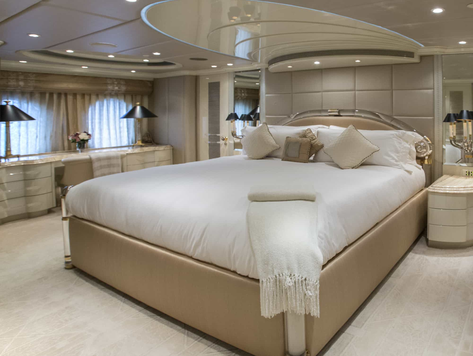 master bedroom suite onboard a luxury yacht complete with cream and white furnishings