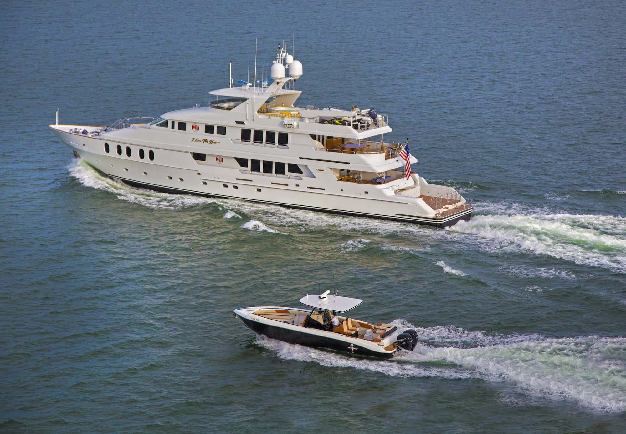 large luxury yacht running with small tender cruising beside