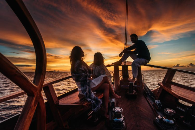family on bow of yacht at sunset