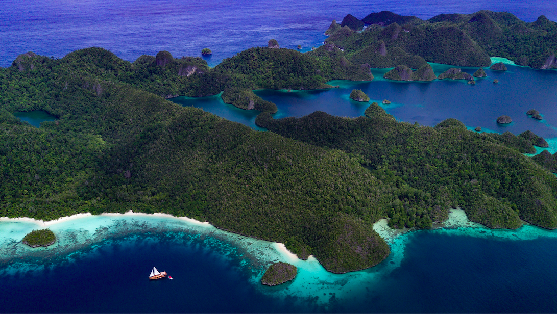 Bird's eye view of sailing yacht Sequoia sailing in the saphire waters surrounding the Indonesian Islands.