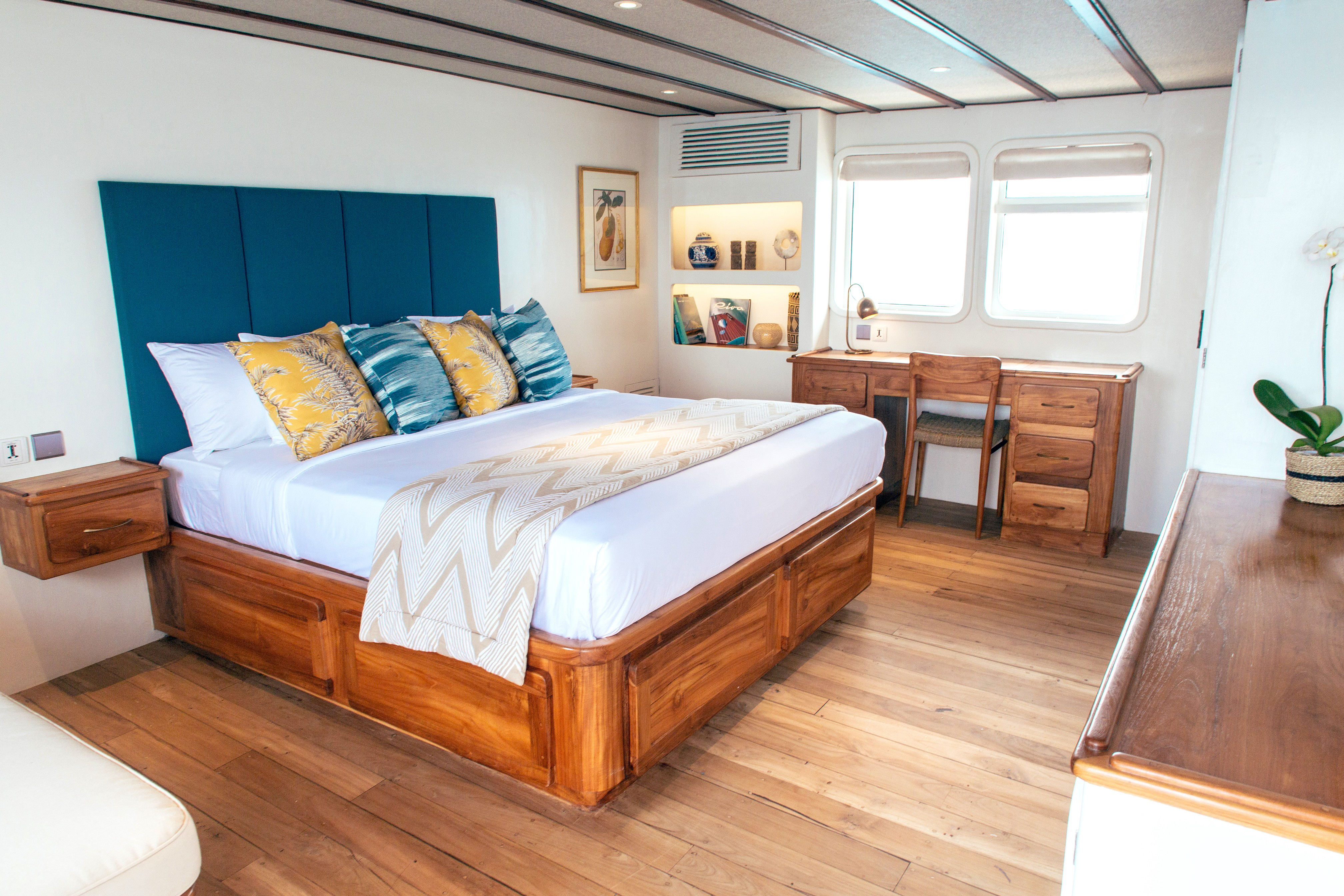 master bedroom onboard a luxury yacht in tasteful light colours and modern teak.