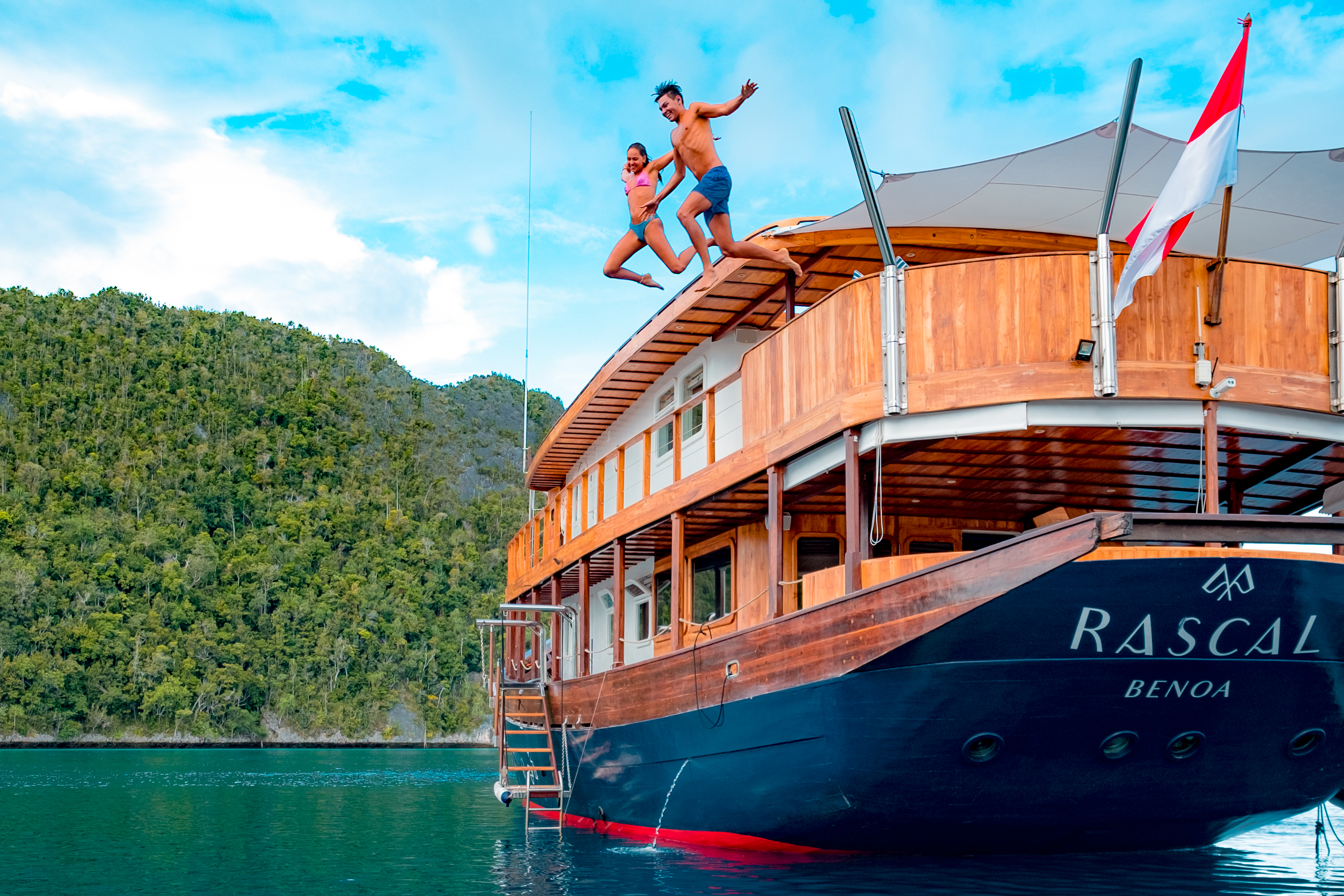couple jumping off the top deck of yacht Rascal