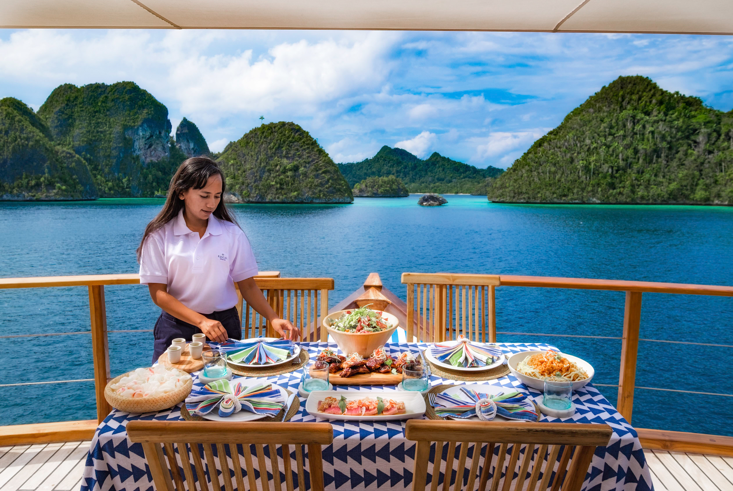 stewardess sets the table on aft deck of yacht in Indonesia