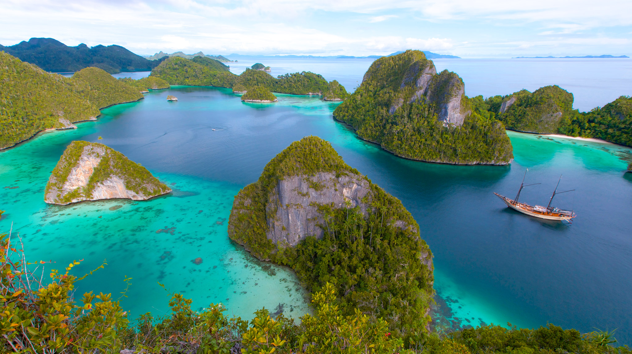 aerial shot of the islands of Raja Ampat with turquoise waters and luxury phinisi yacht Silolona at anchor
