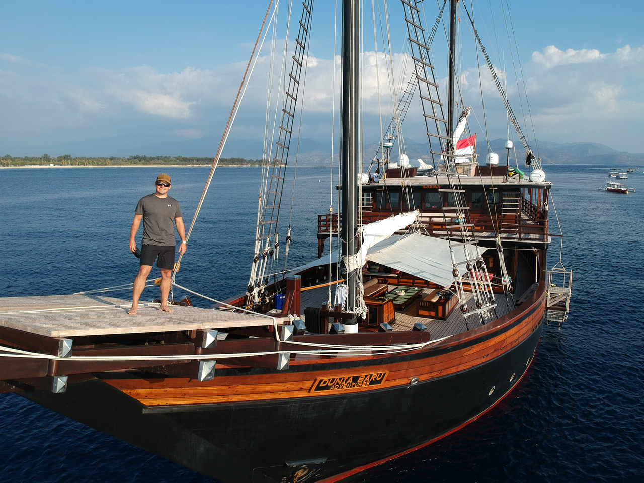 man smiling on bow of luxury wooden yacht Dunia Baru in Indonesia