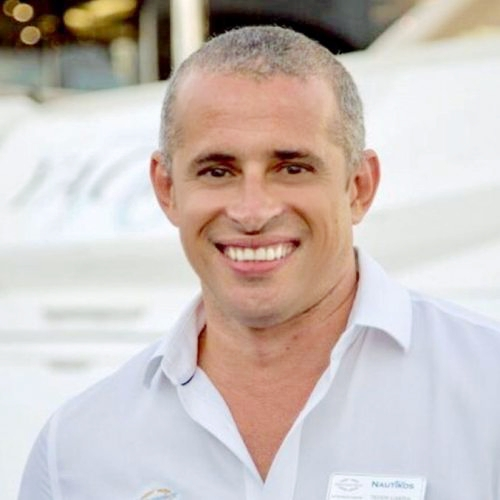 man smiling in front of yacht