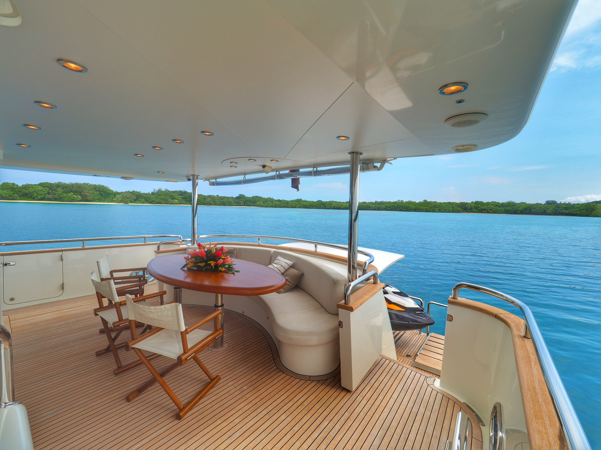 after deck of yacht with blue waters and trees in background