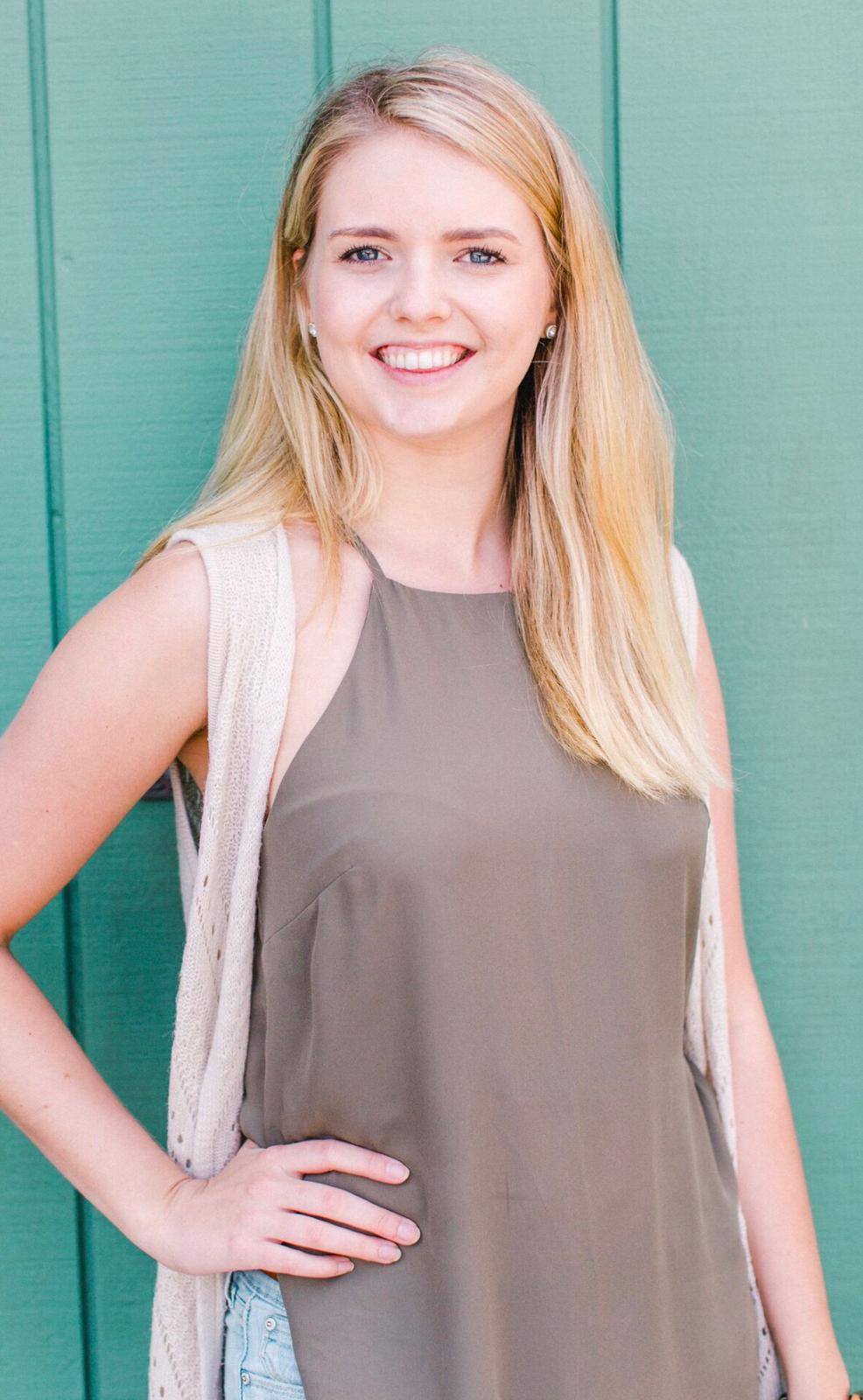 blonde woman smiling in front of teal wall