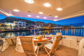 aft deck of a yacht with table set for dinner at dusk