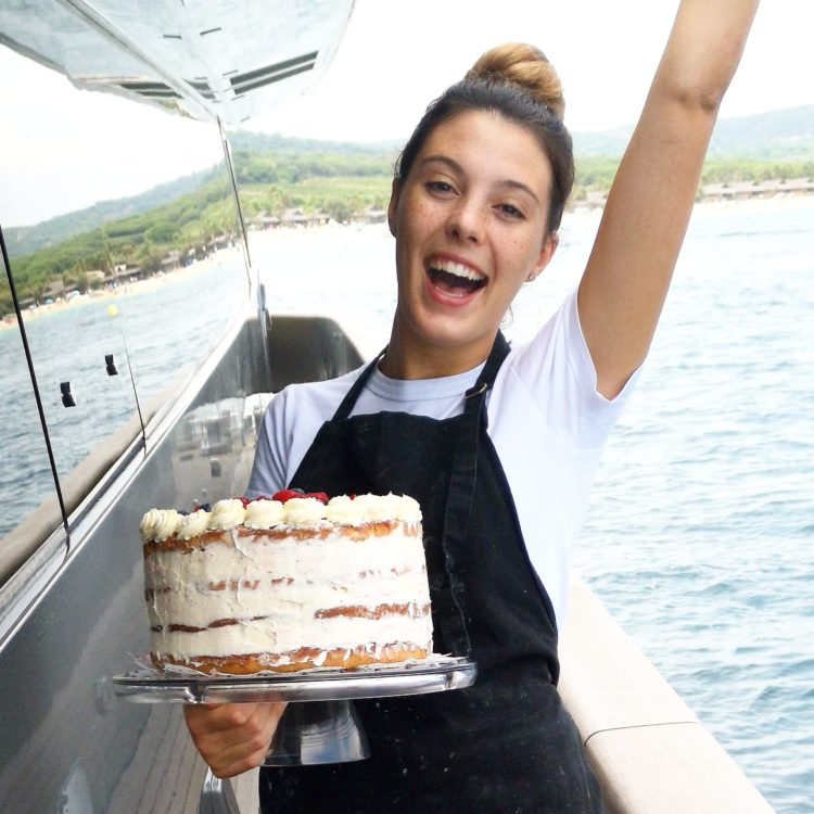 young blonde female yacht chef Jessica Alcock holding a cake on a yacht