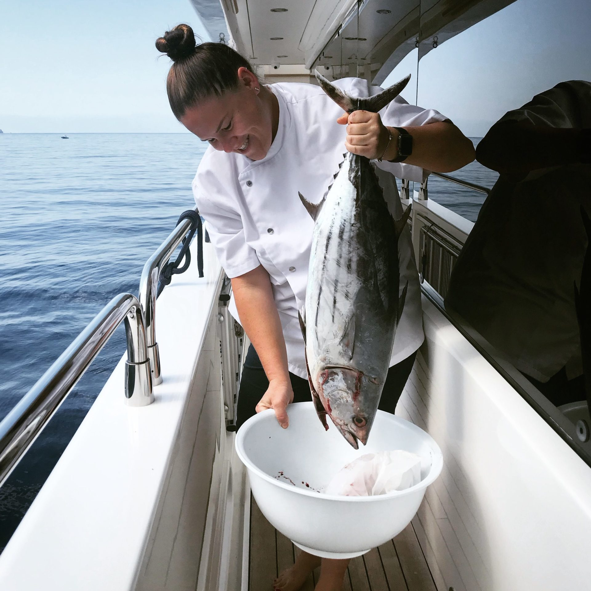 Chef Jeanri in chef jacket smiling down while holding large fish onboard a yacht