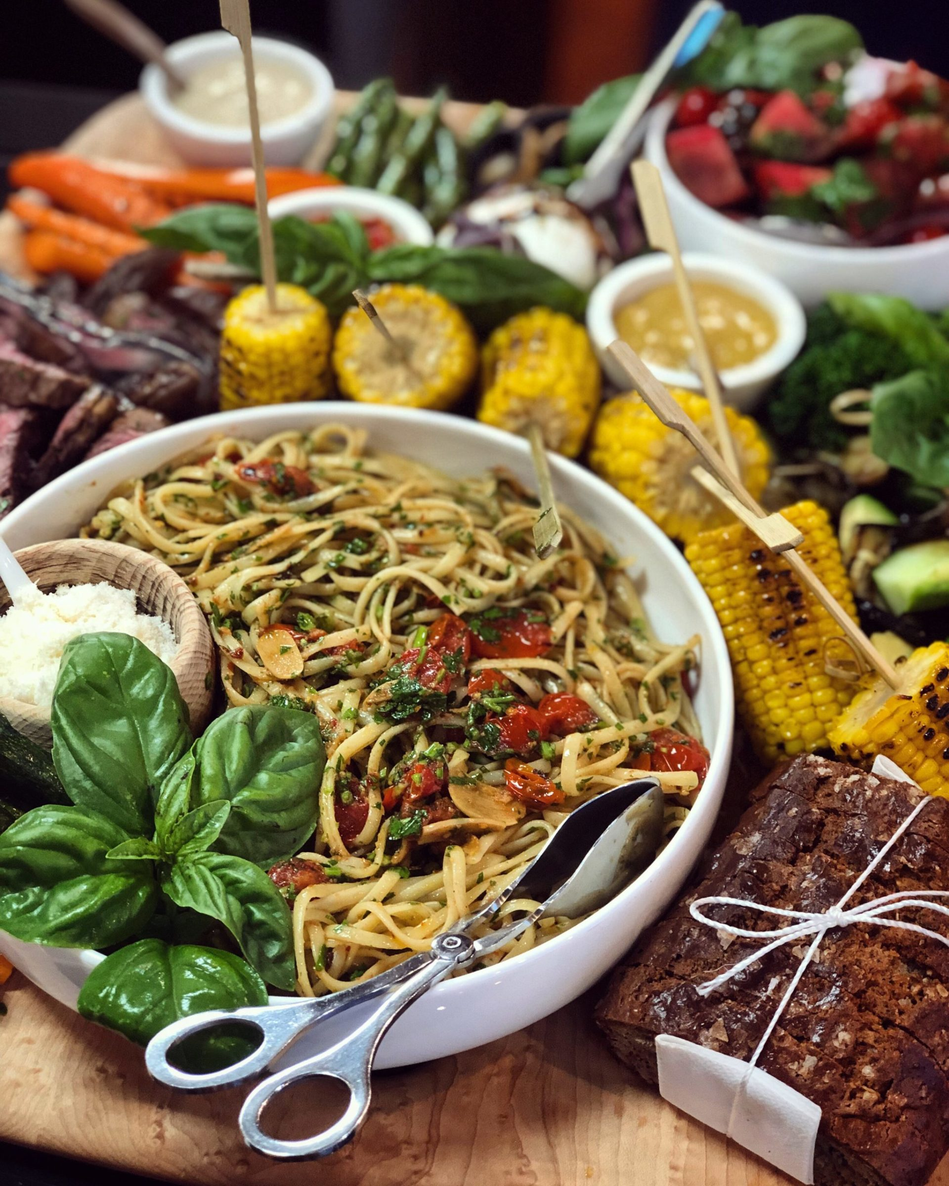 a display of food, big bowl of fresh spaghetti and barbecue corn and bread and salad