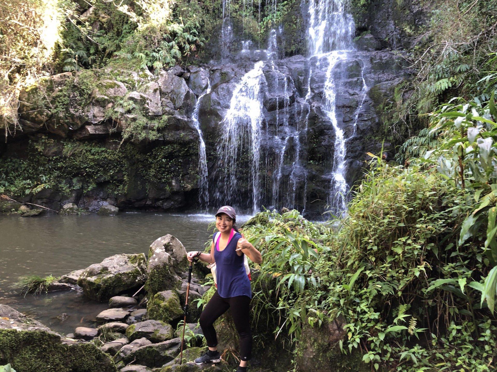 Renee Tsang hiking at foot of waterfall in Hawaii