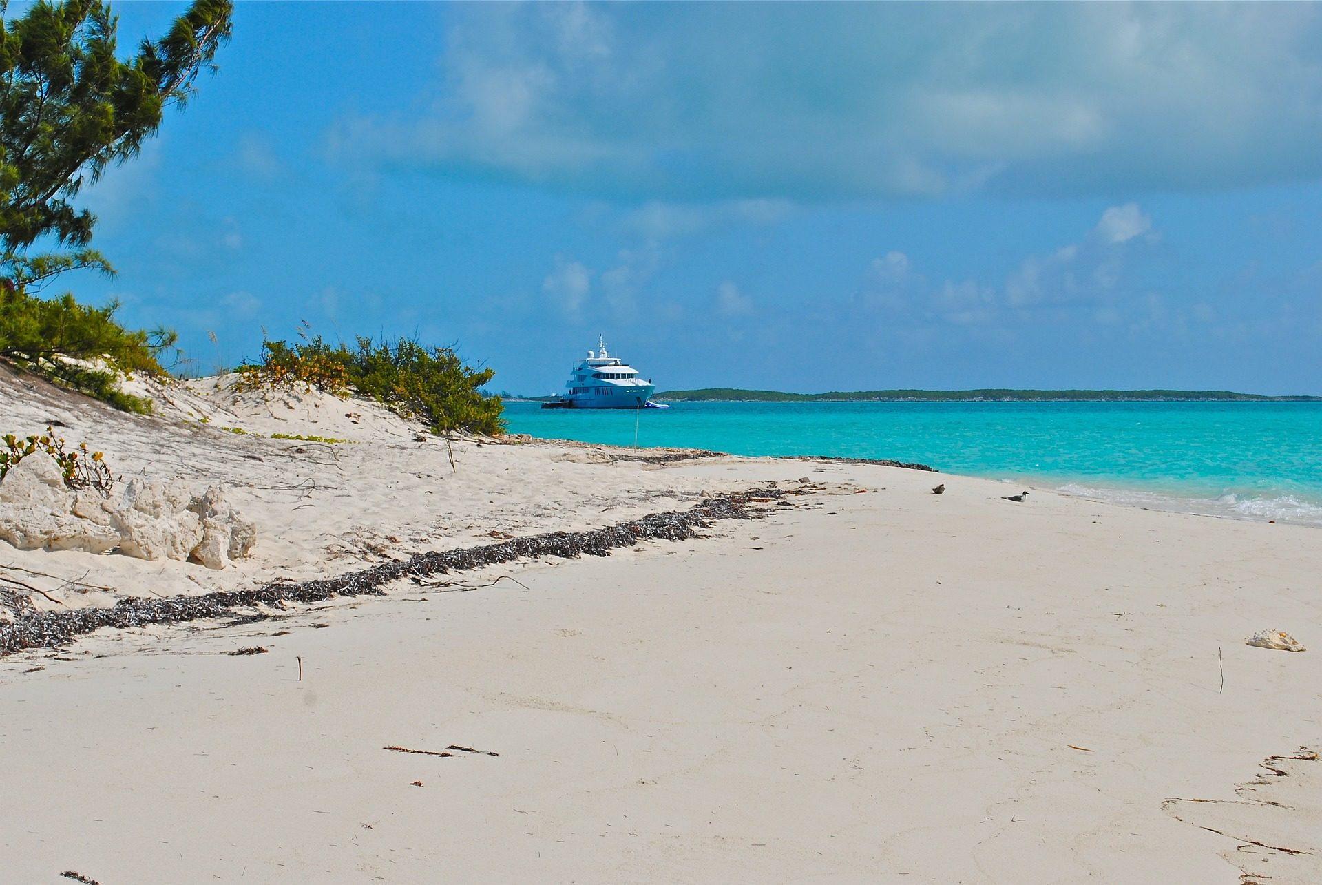 white sand beach of the Bahamas with turquoise waters and superyacht in the background