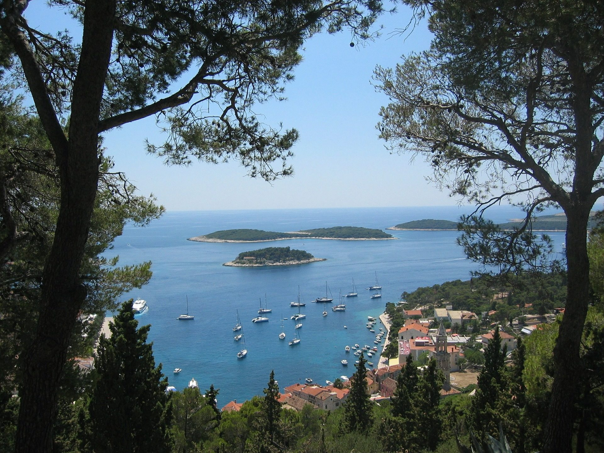 view of Hvar from up on a cliff with little islands and yachts dotted along the shore