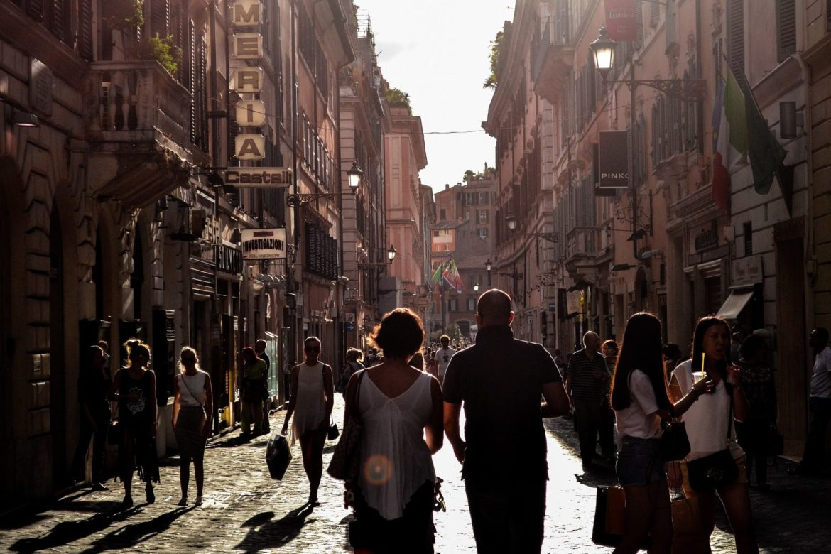 silhouette of man and woman at sunset walking amongst shops in Naples, Italy