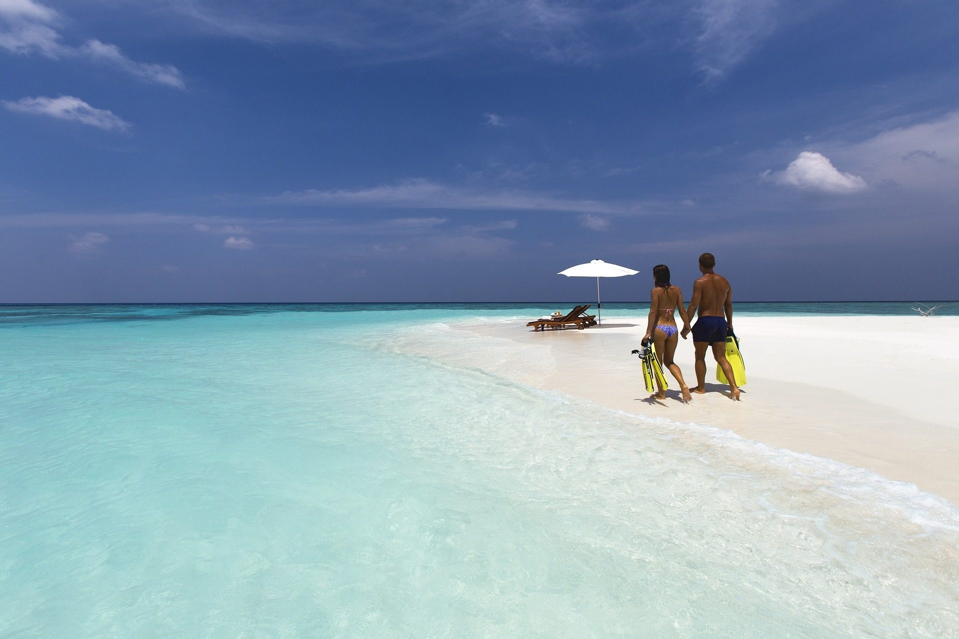 couple on deserted white sand beach carrying scuba gear