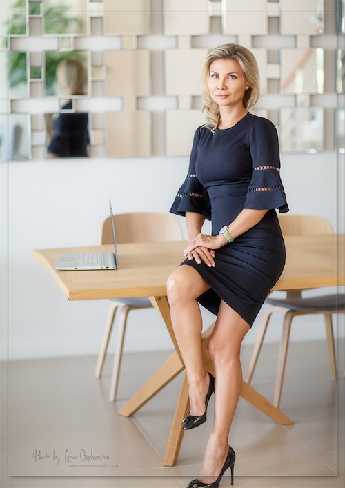 Irina Duisimbekova, Co-Founder and CEO of Aerojet ME sitting on desk in blue dress