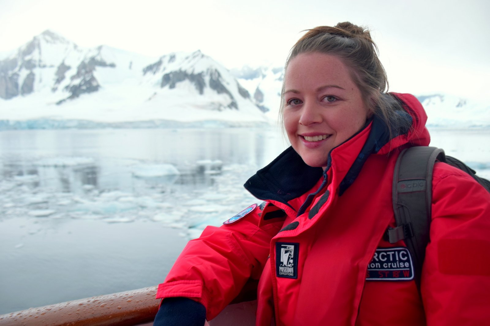 Megan Jerrard on a boat in Antarctica with snowy mountains behind