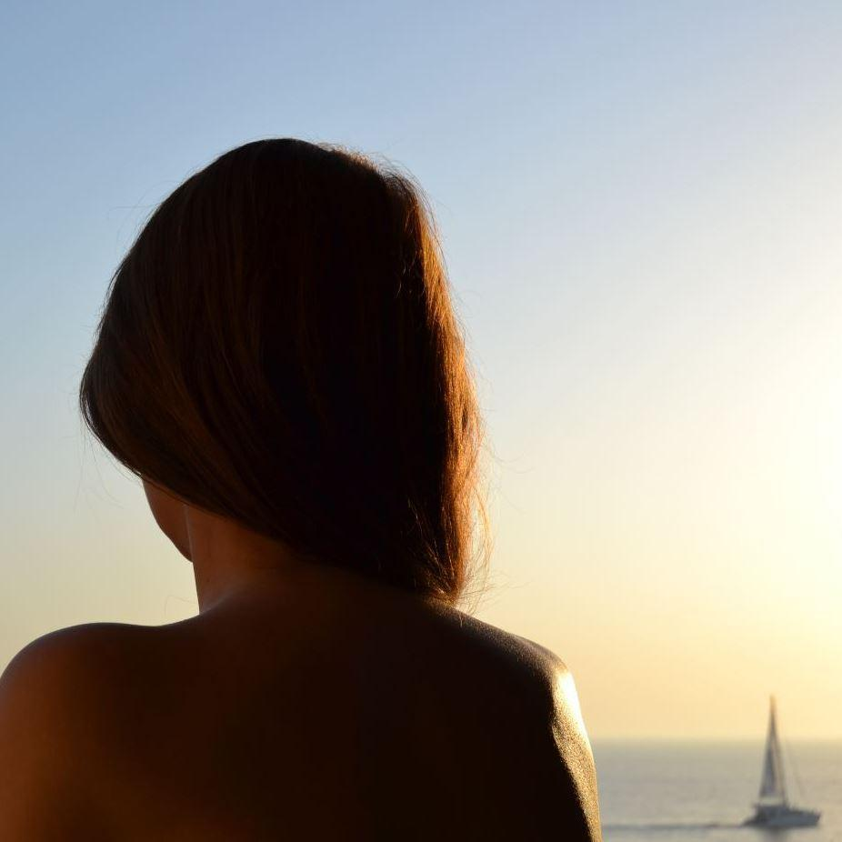 photo of woman's head from behind looking off into the sunset