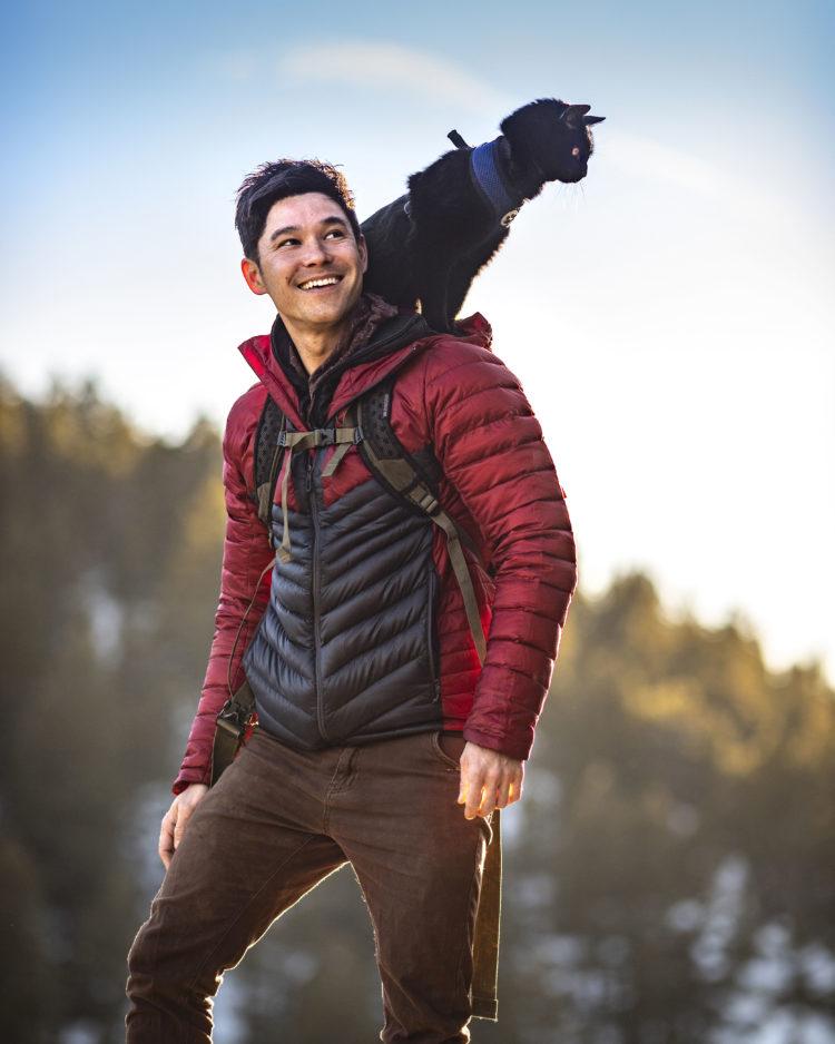 Film director JJ Yosh stands on a mountainside with his cat perched on his shoulder