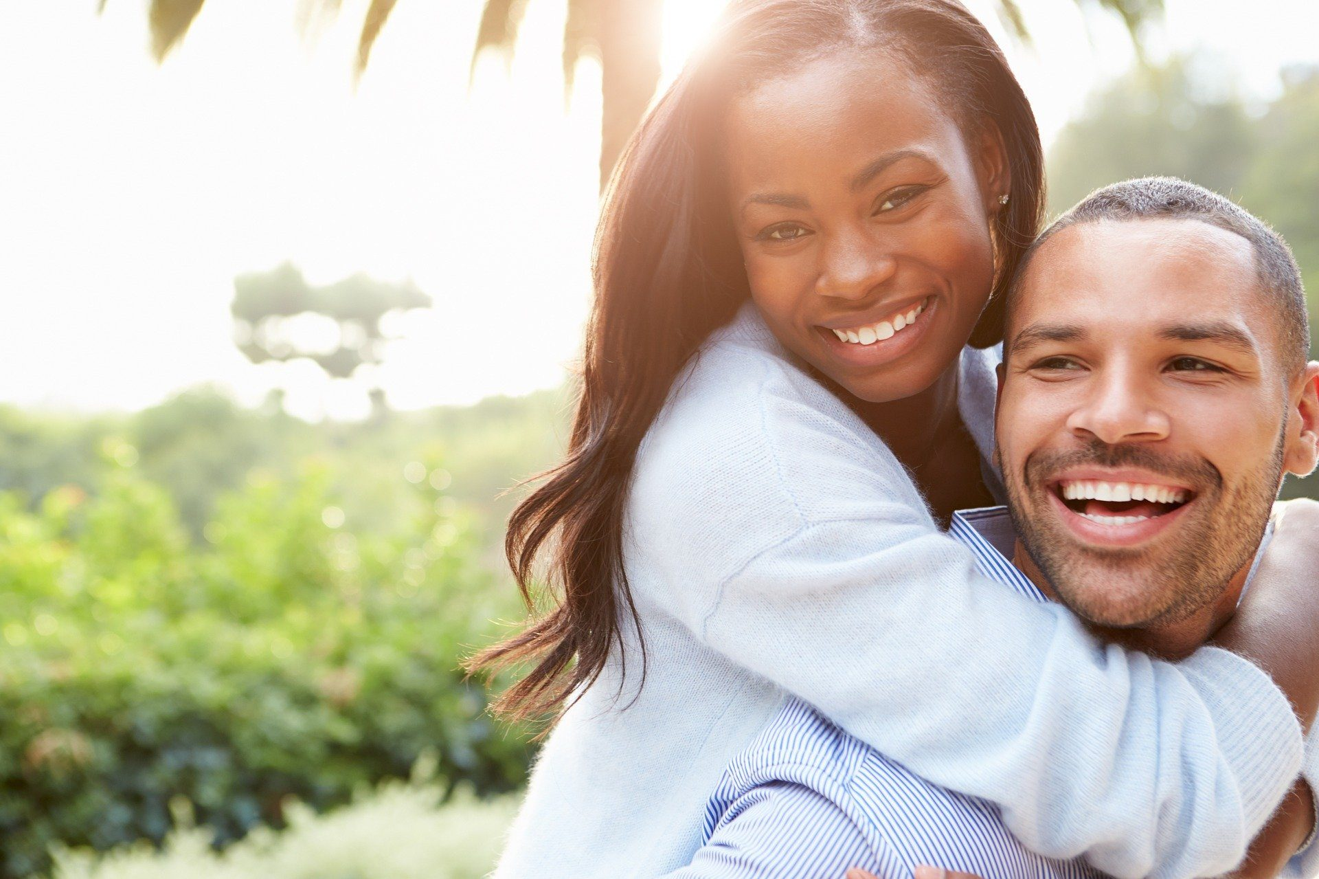 Black couple smiling at camera while man gives the woman a piggy back ride with sun behind them