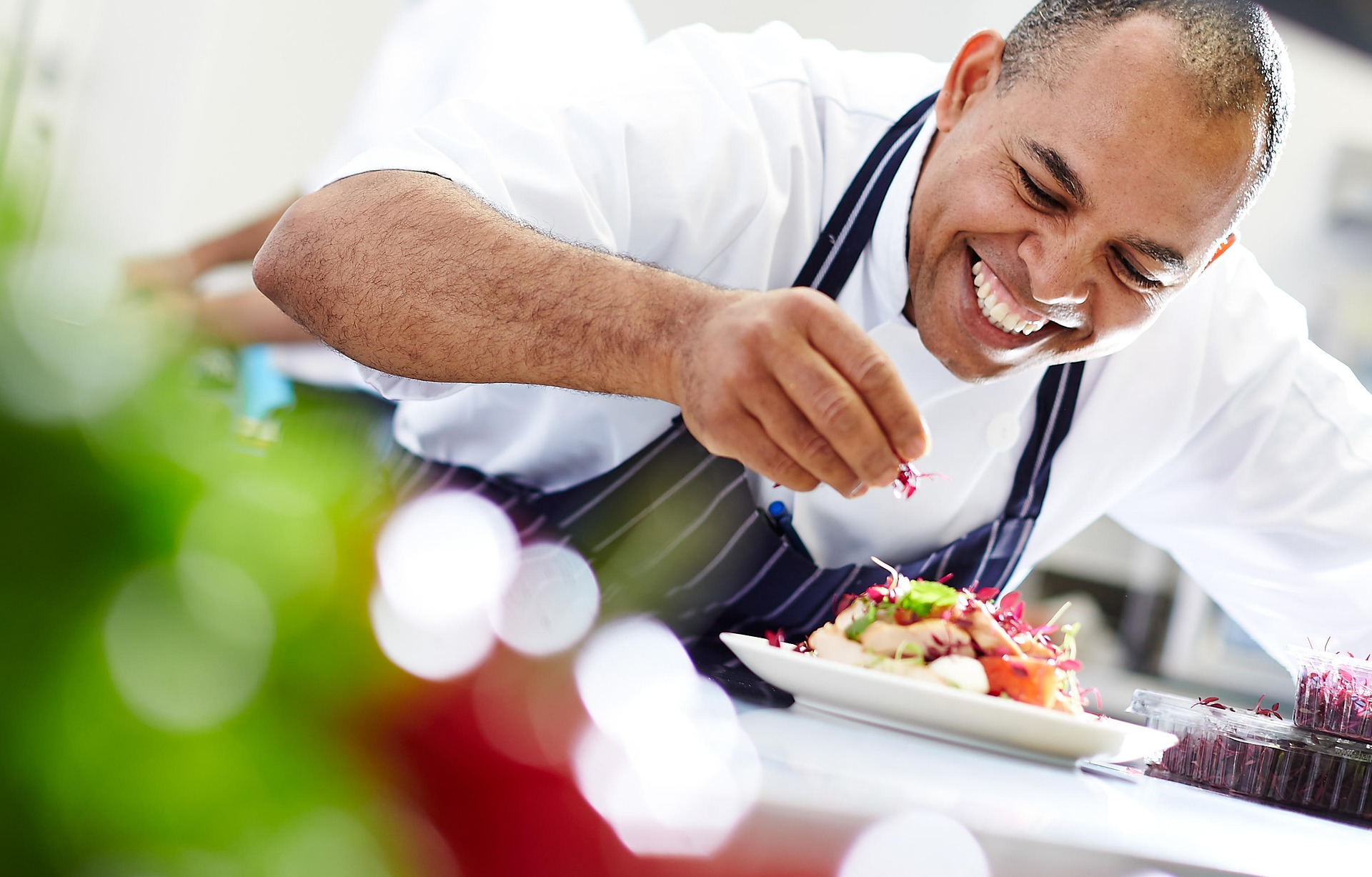 Male chef smiling as he puts the finishing touches on a dish