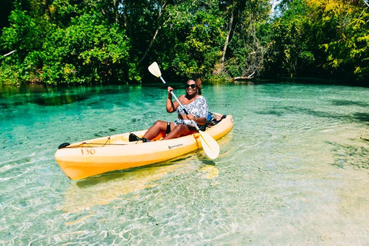 A Black woman paddling in a yellow kayak down the Weeki Wachee River in Florida