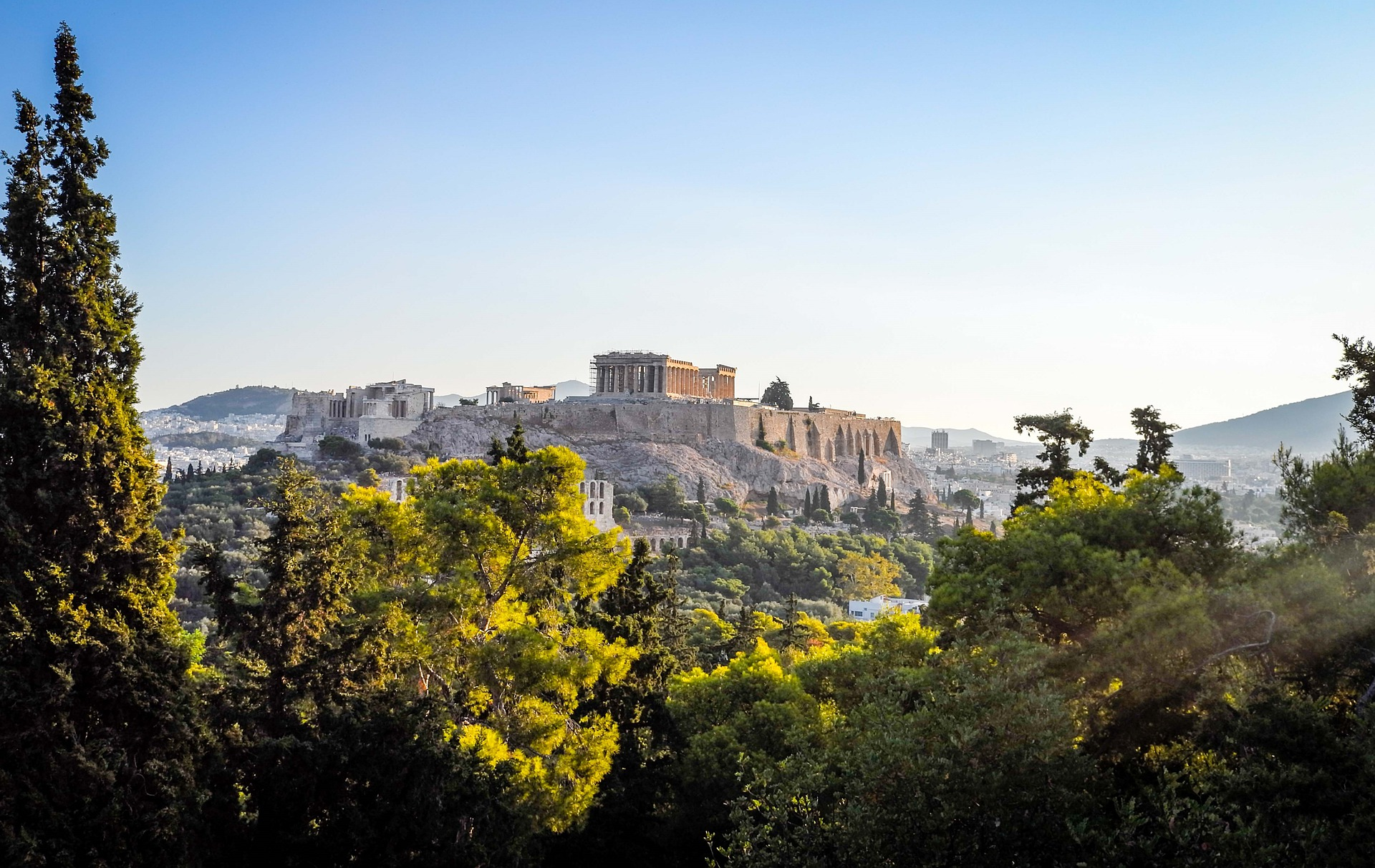 shot of the Acropolis in Athens at a distance with trees in the foreground