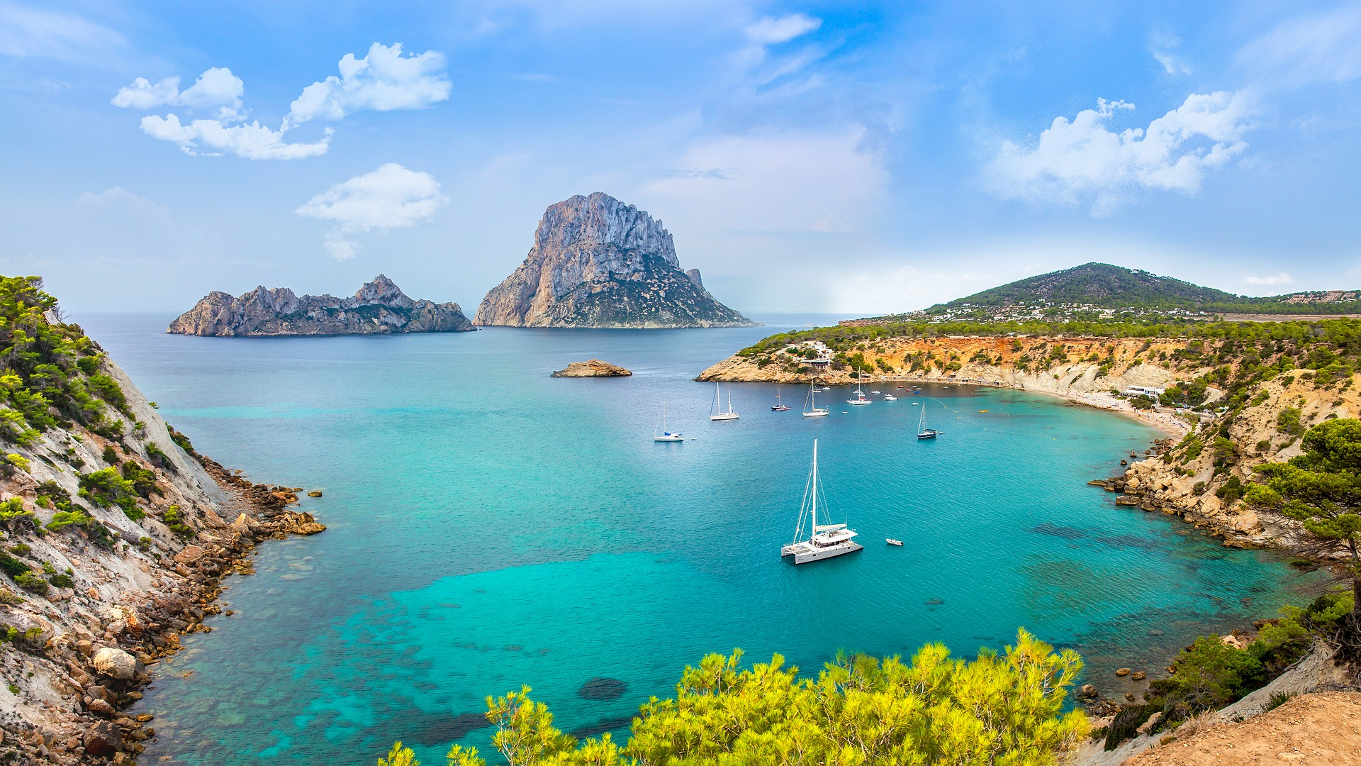 aerial view of beach and boats at anchor in Ibiza with islands in the background