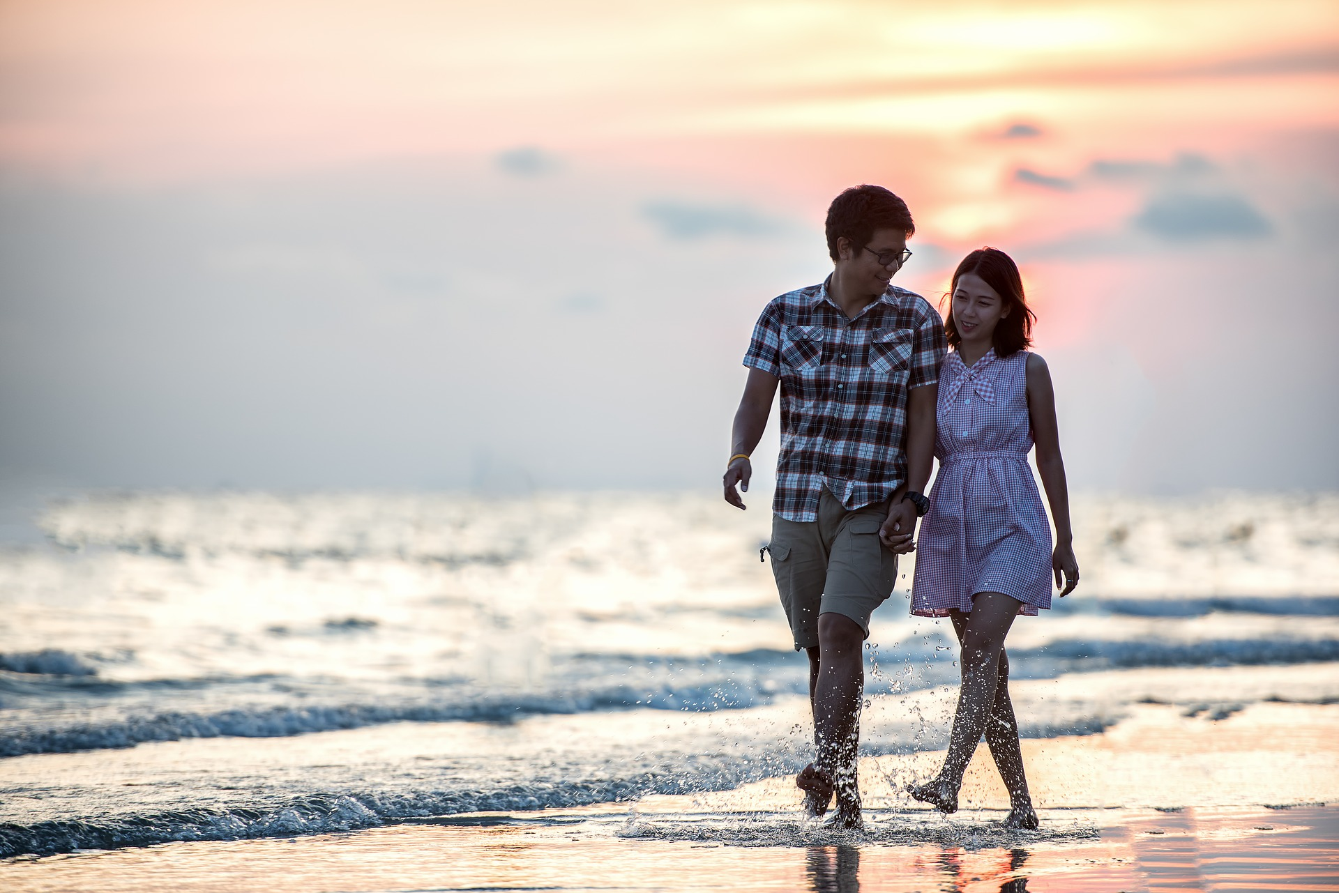 Asian couple walking on the beach at sunset