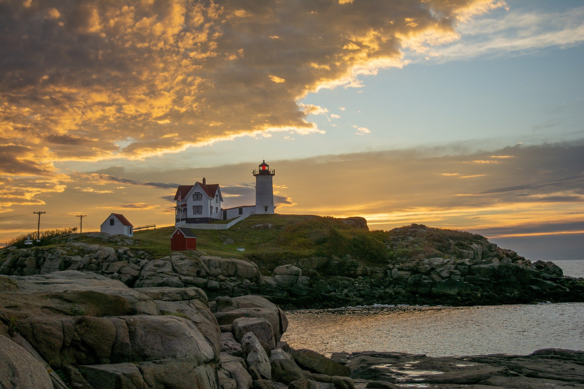 lighthouse at sunset on rocky cliff off coast of New England