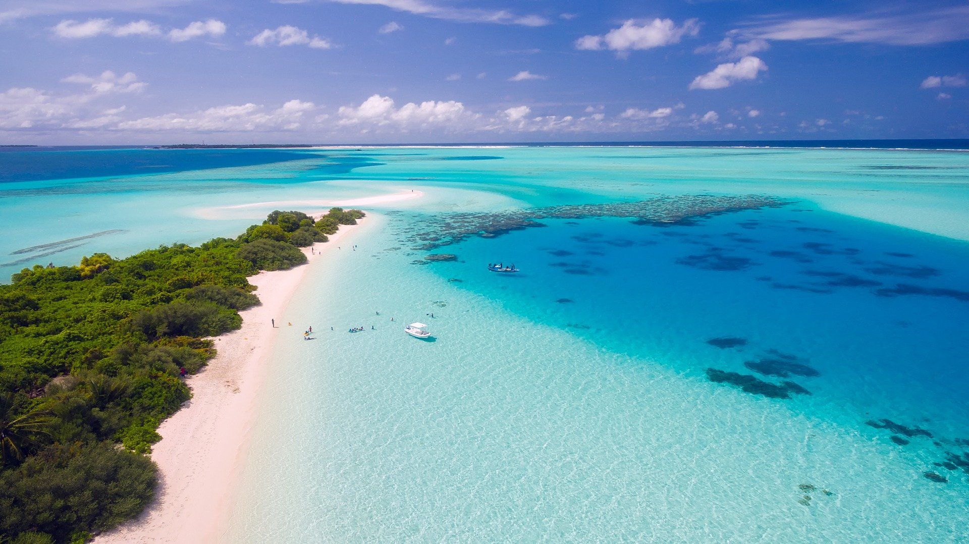 white sand beach and turquoise waters of the Maldives with coral reed and boats visible