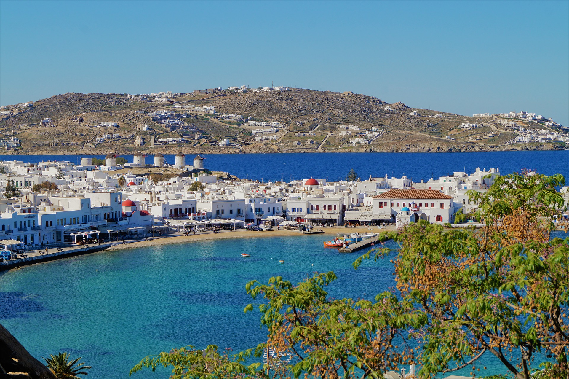 shot of Mykonos harbour with turquoise blue waters and white washed buildings with mountains in the background